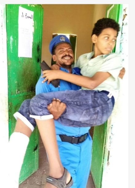 بالصورة : شرطي بأحد مراكز امتحانات شهادة الأساس يحمل تلميذاً مصابا برجله إلى قاعة الامتحان