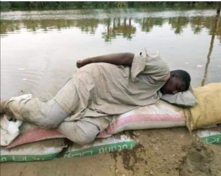 """بالصورة.. شاهد شاب سوداني يغفو على"""" ترس"""" للفيضان أمام النيل يثير إعجاب متابعي المواقع الاسفيرية"""